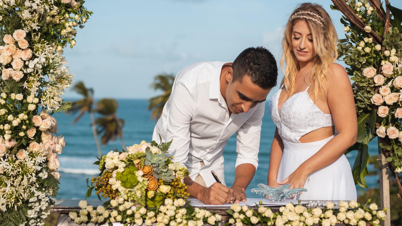 Hochzeitspaar in Blumenkulisse vor dem Meer unterschreibt Dokumente