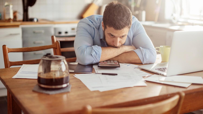 Junger Mann sitzt mit besorgtem Blick vor Dokumenten, Taschenrechner und Laptop, den Kopf in die verschränkten Arme auf den Tisch gelegt