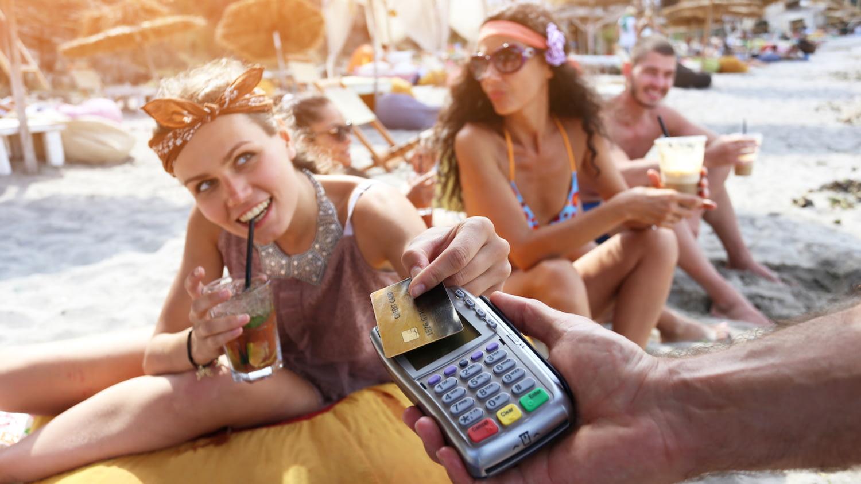 Eine junge Frau sitzt am Strand und bezahlt ihren Cocktail mit Kreditkarte.