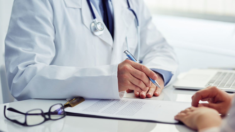 Arzt legt einem Patienten eine Einwilligungserklärung zur Unterschrift vor