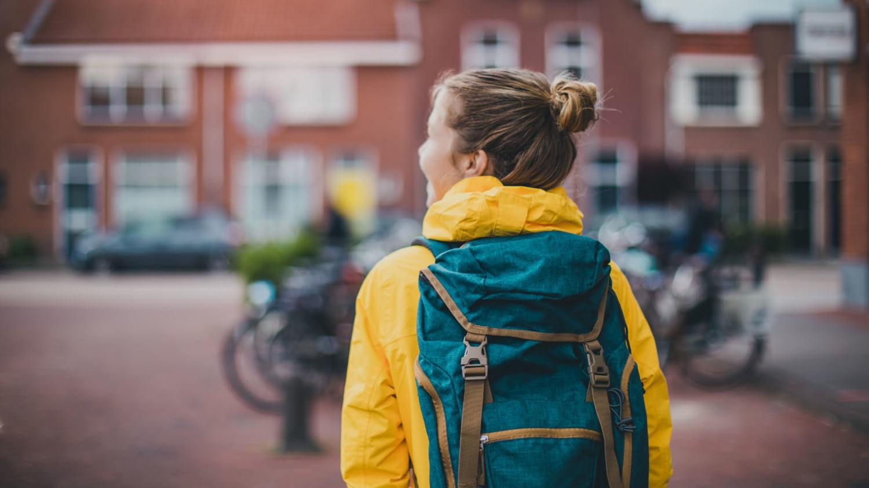 Rückansicht einer Schülerin mit Rucksack auf dem Weg nach Hause