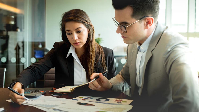 Geschäftsfrau und Geschäftsmann blicken gemeinsam auf Papiere mit verschiedenen Zahlen und Charts.