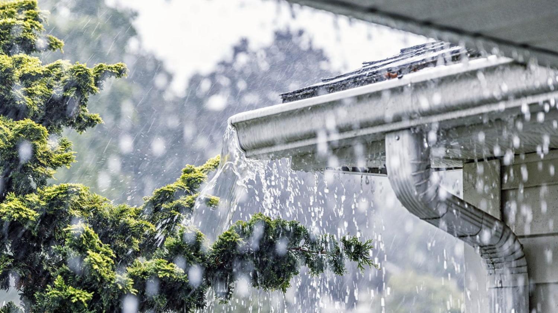 Die Dachrinne an einer Hausecke läuft über durch starken Regen