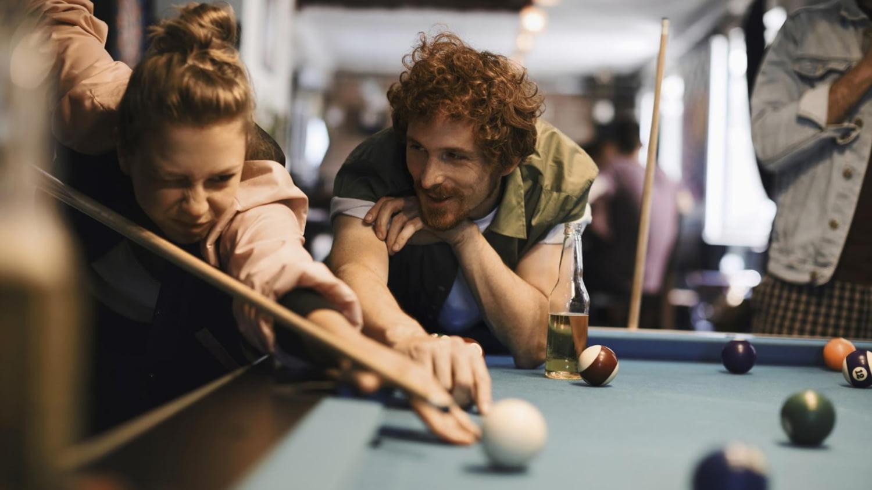 Junger Mann und junge Frau am Billardtisch