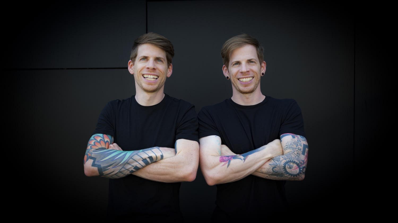 Zwei junge Männer stehen nebeneinander mit jeweils spiegelverkehrten Tattoos und Seitenscheiteln