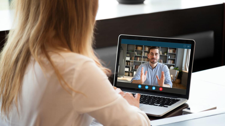 Eine Frau sieht einem Mann auf einem Tablet-Bildschirm zu wie er ihr etwas erklärt