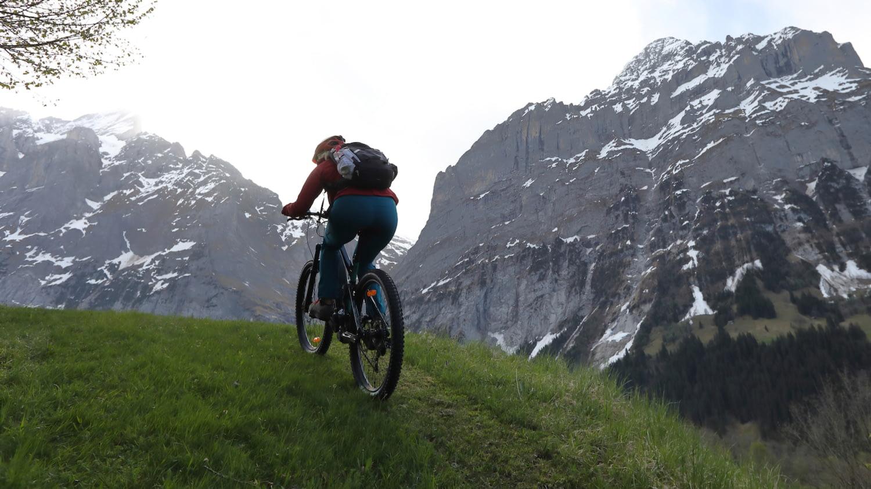 Blick von hinten auf eine Frau, die mit einem Pedelec einen Hügel hochfährt vor einem Bergpanorama