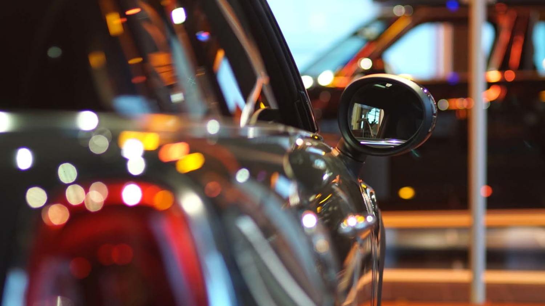 Ein Auto steht mit einem weiteren im Showroom eines Autohauses