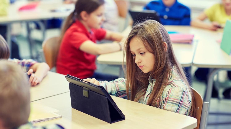 Eine Schülerin sitzt in einem Klassenzimmer und tippt auf den Bildschirm eines Tablet-PCs