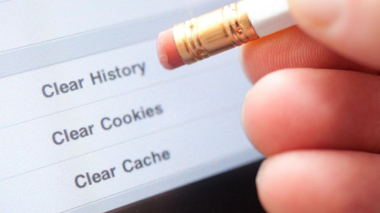 Jemand hält einen Bleistift mit Radiergummi vor einen PC-Bildschirm, um symbolisch Cookies zu löschen