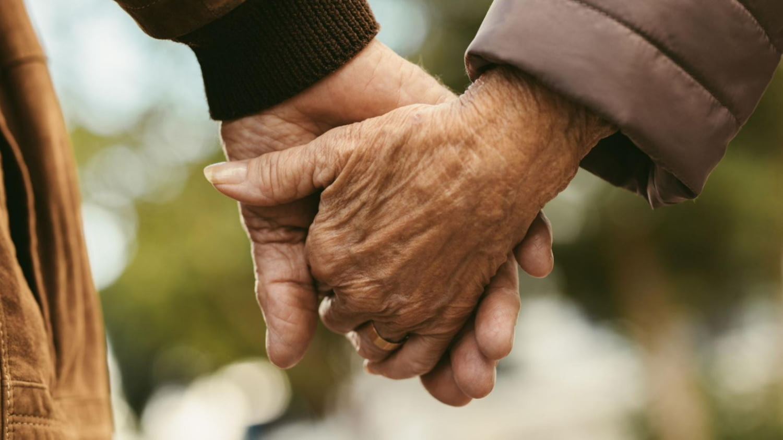 Detailaufnahme eines älteren Paares, das sich an den Händen hält