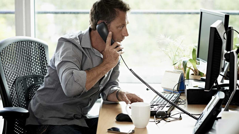 Mann mit Telefonhörer in der Hand blickt besorgt auf den PC-Bildschirm
