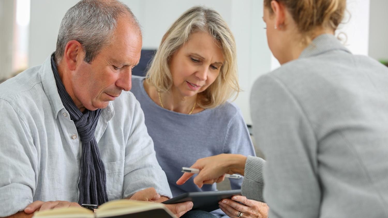 Ein Ehepaar lässt sich von einer Notarin beraten