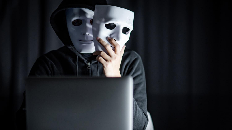 Mann im Kapuzenpulli sitzt vorm Laptop und trägt eine Maske im Gesicht und eine zweite in der linken Hand