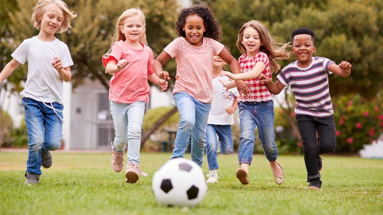 Sechs Kinder laufen lachend auf einen Fußball im Vordergrund zu