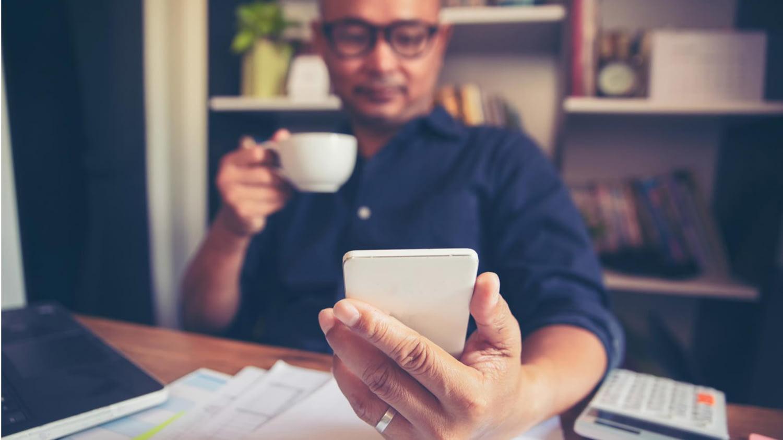 Mann trinkt Kaffee am heimischen Schreibtisch und blickt auf sein Smartphone