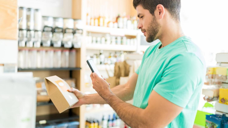 Eine Mann steht im Supermarkt und blickt auf das Display seines Smartphones