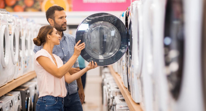 Verkäufer führt älterem Ehepaar neue Waschmaschine vor
