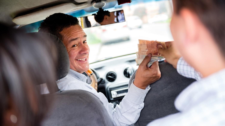 Ein Taxifahrer wird am Fahrziel bezahlt und erhält auch ein Trinkgeld