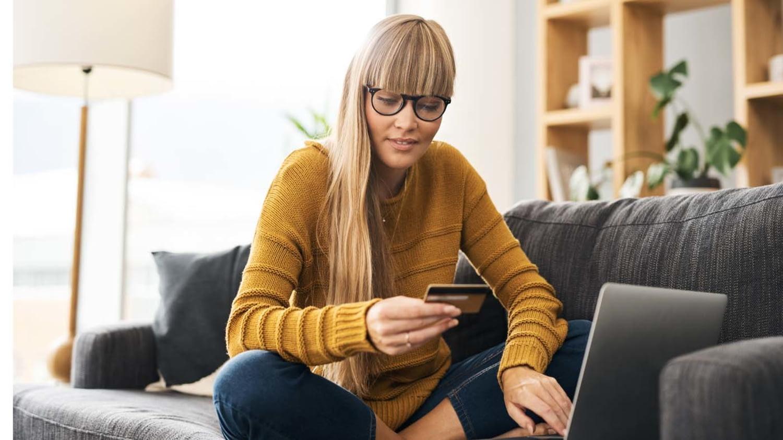 Eine Frau hält ihre Kreditkarte in einer Hand und tippt mit der anderen etwas in den Laptop