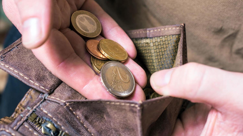 Ein Arbeiter in Latzhose und mit Handschuhen zählt 500-Euro-Scheine