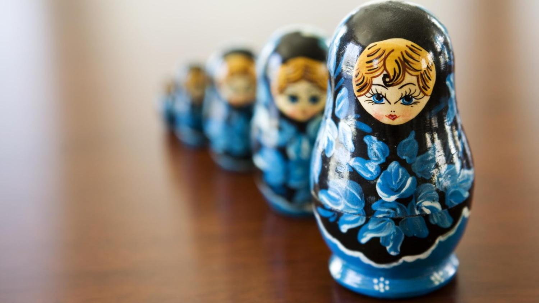 Fünf Matroschka-Puppen stehen hintereinander auf einem Tisch