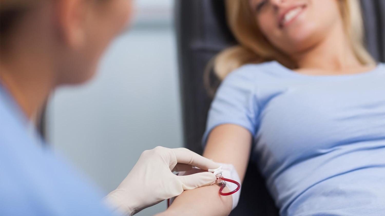 Eine Krankenschwester nimmt einer Frau eine Blutspende ab