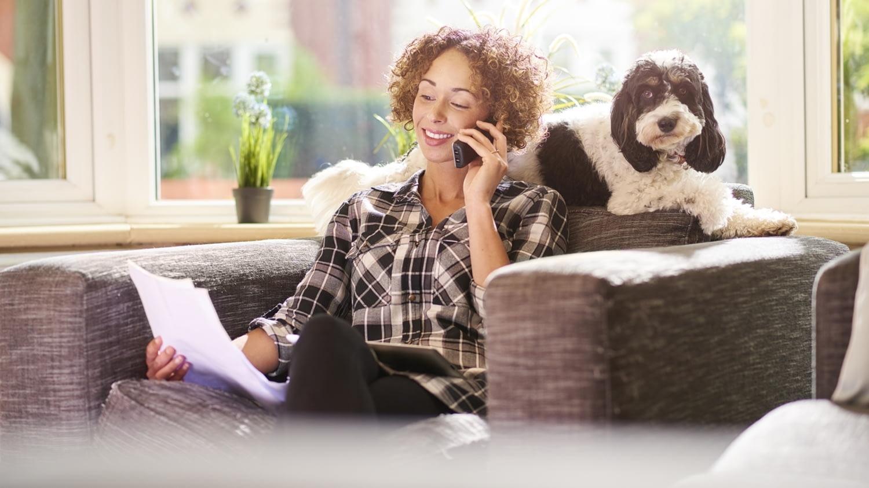 Frau sitzt telefonierend auf dem Sofa und blickt dabei auf ihre Gehaltsabrechnung