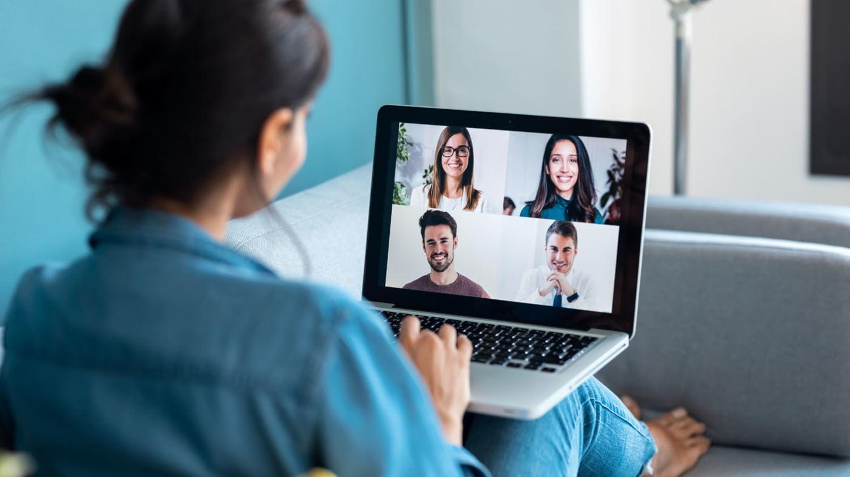 Junge Frau hält auf dem Sofa sitzend eine Videokonferenz mit vier Kolleg*innen