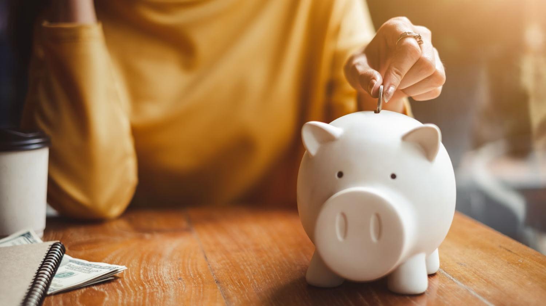 Eine Frau steckt eine Münze in den Schlitz eines Sparschweins