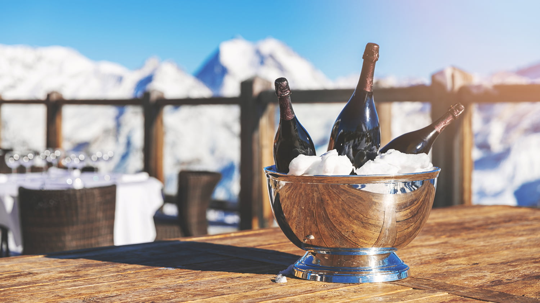 Drei Champagner-Flaschen im Kühler, die auf einem Tisch vor einem winterlichen Bergpanorama steht