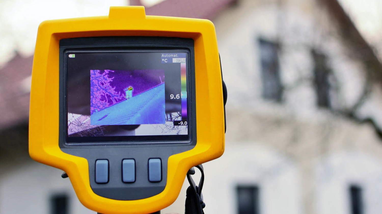 Thermografie-Aufnahme eines Wohnhauses im Display einer Wärmebildkamera, im Hintergrund ist unscharf das Gebäude zu sehen