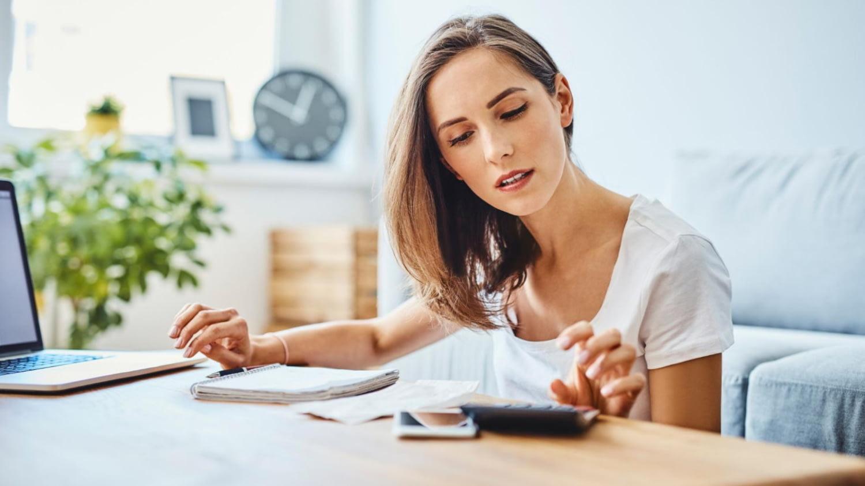 Junge Frau am Laptop rechnet ihre Kosten mit einem Taschenrechner nach