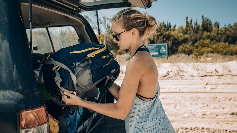 Eine Frau packt einen Rucksack in einen fast vollen Kofferraum