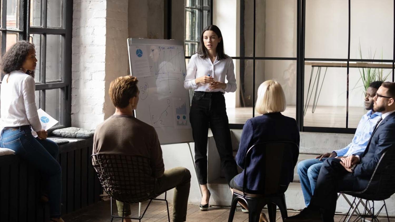 Business-Dame steht vor einem Flipchart und berät eine Gruppe von Existenzgründern