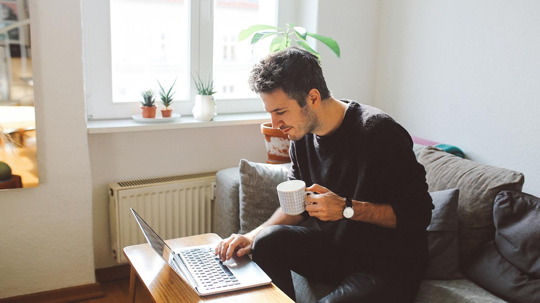 Mann sitzt auf dem Sofa und arbeitet mit dem Laptop auf dem Wohnzimmertisch