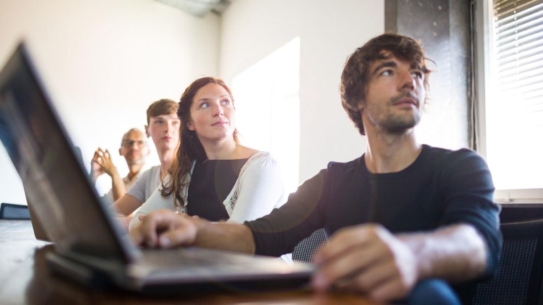 Vier erwachsene Kursteilnehmer in einem Klassenraum, die ihrem Dozenten aufmerksam zuhören
