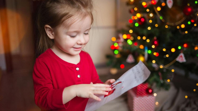 Kleines Mädchen blickt auf einen beschriebenen Zettel, im Hintergrund ein Weihnachtsbaum
