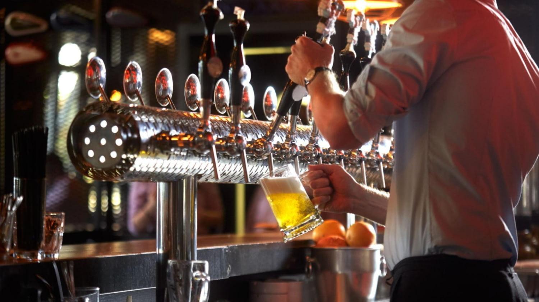 Mann hinter einem Bartresen zapft ein Glas Bier