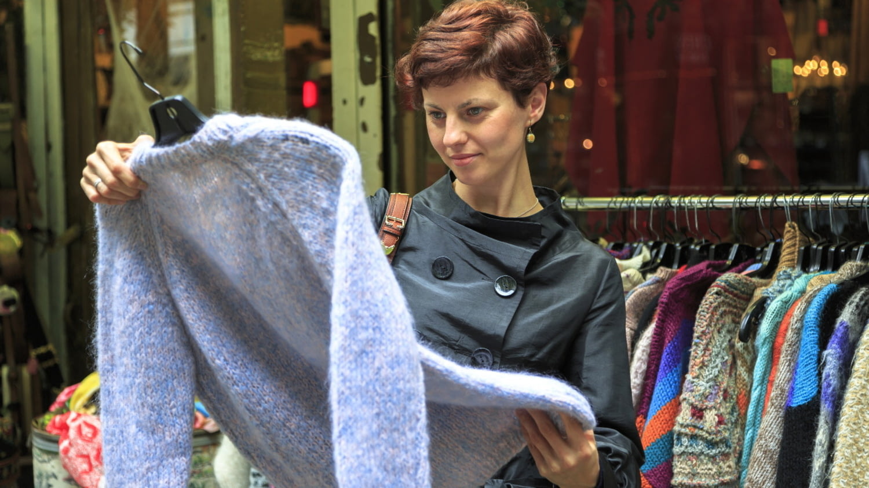 Eine junge Frau betrachtet einen Pullover beim Einkaufen.
