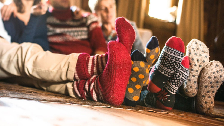 Eine Familie sitzt mit dicken Wollsocken nebeneinander auf dem Wohnzimmerboden