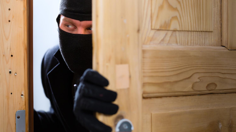 Ein Einbrecher schaut durch einen Türspalt eine Wohnung