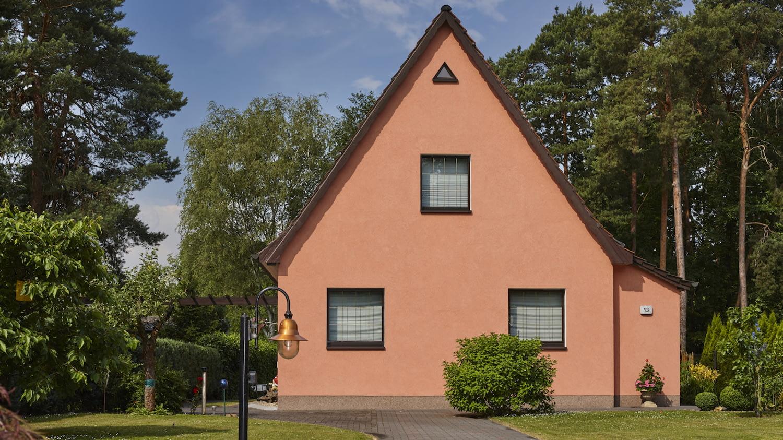 Typisches Einfamilienhaus mit Spitzgiebel aus den 1950er Jahren mit frisch gestrichener lachsfarbener Fassade.
