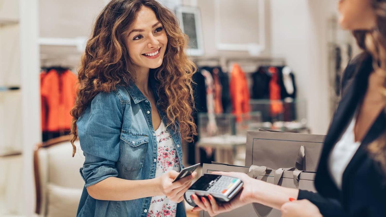 Eine junge Frau zahlt an der Kasse eines Modegeschäfts mit ihrer Kreditkarte