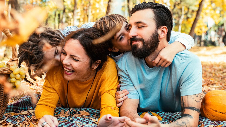 Bei einem Ausflug im Wald umarmen auf einer Decke zwei Kinder ihre Eltern