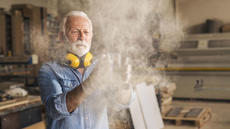 Ein älterer Tischler klopft seine staubigen Handschuhe aus
