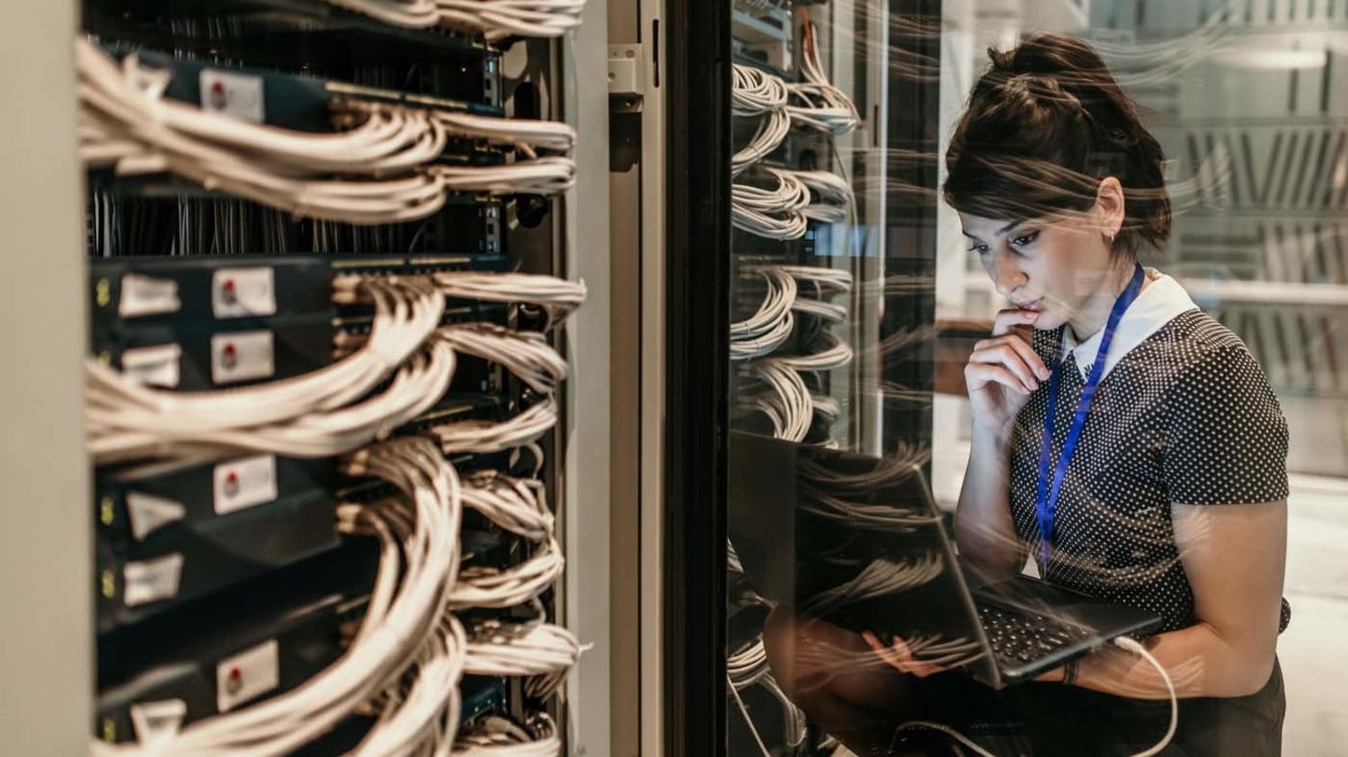 Vor Regalen mit Servern sitzt eine Frau und blickt nachdenklich auf den Bildschirm ihres Notebooks