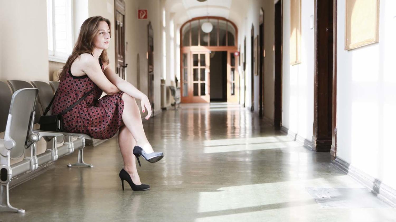 Eine junge Frau im Kleid sitzt im Flur eines Amtsgebäudes und wartet
