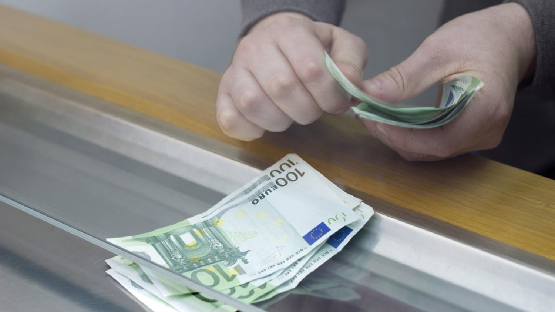 Eine Hand an einem Schalter liegt auf vier aufgefächerten Geldscheinen