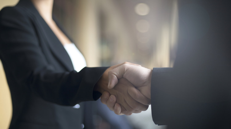 Mann und Frau besiegeln Absprache mit per Handschlag